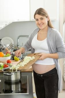 スープに野菜を入れる可愛い笑顔の妊婦さん