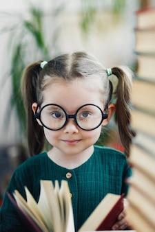 Милая улыбающаяся девочка дошкольного возраста с ямочками на щеках в круглых больших очках с красной книгой