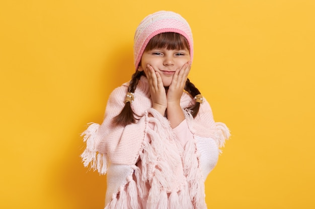 Милая улыбающаяся дошкольница в розовой вязаной шапке и уютном пончо, изолированном на желтой стене, смотрит вперед