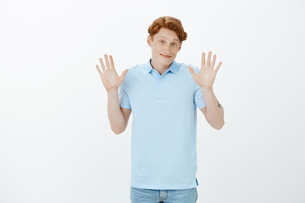 Cute smiling redhead man apologising, raising hands up unaware, don't know