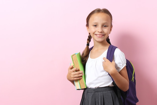 Cute smiling schoolgirl with a school backpack on a colored background