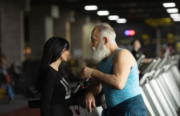 Cute smiling senior couple exercising in gym.