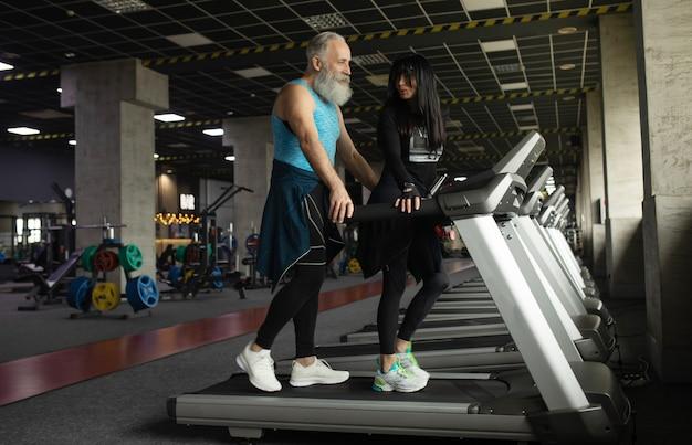 Cute smiling senior couple exercising in gym.