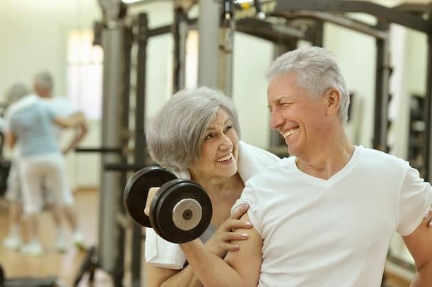 체육관에서 운동하는 귀여운 웃는 노부부