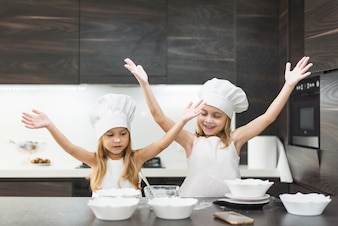 Cute smiling sisters in kitchen enjoying while preparing food