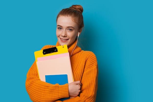 빨간 머리와 주근깨가있는 귀여운 웃는 학생은 파란색 배경에 포즈를 취하고 음악을 듣는 동안 주황색 스웨터를 입은 일부 책을 들고 있습니다.