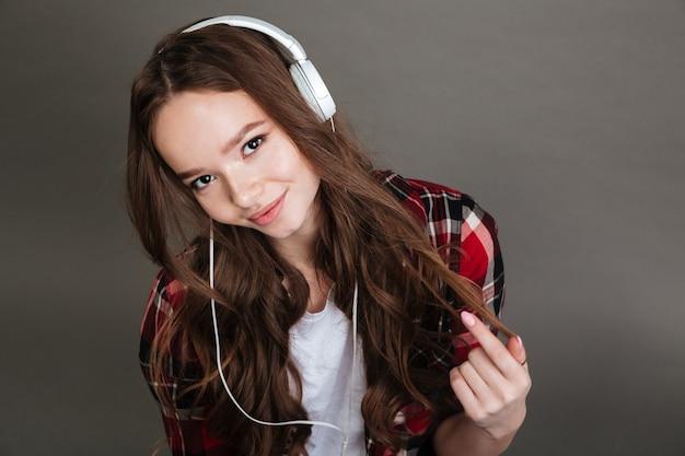 Милая улыбающаяся девочка-подросток в наушниках