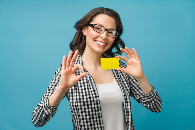 Cute smiling woman in dress shirt and eyeglasses showing credit card in hand for financial and