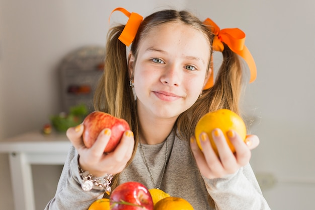 Cute smiling woman holding red apple and an orange in hands
