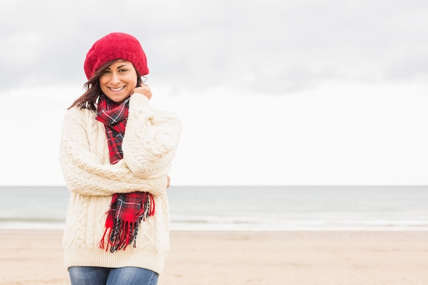 Симпатичная улыбающаяся женщина в стильной теплой одежде на пляже