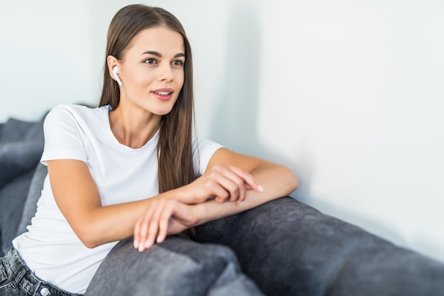 Cute smiling woman lying on couch while listening via airpods to music in bright living room