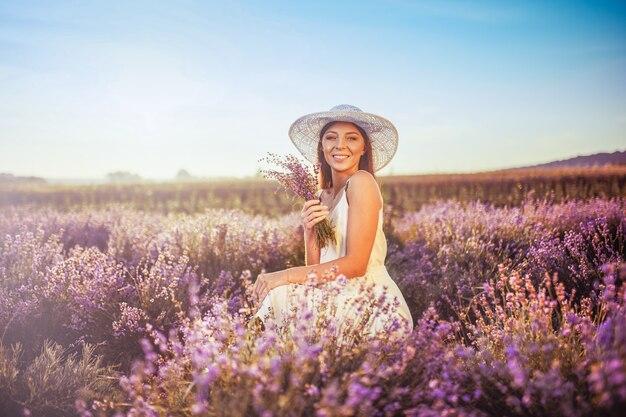 Милая улыбается женщина, отдыхая в поле лаванды. Premium Фотографии