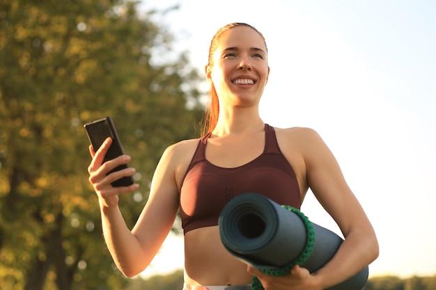 スマートフォンを使用してトラックスーツを着て、公園で日没時にヨガマットを保持しているかわいい笑顔の女性。