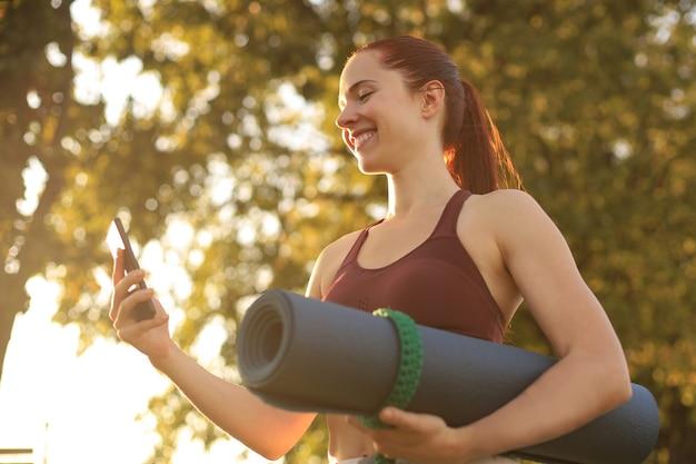 스마트폰을 사용하여 운동복을 입고 공원에서 일몰에 요가 매트를 들고 있는 귀여운 웃는 여자.