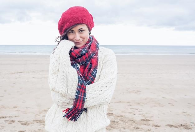 Симпатичная улыбающаяся молодая женщина в стильной теплой одежде