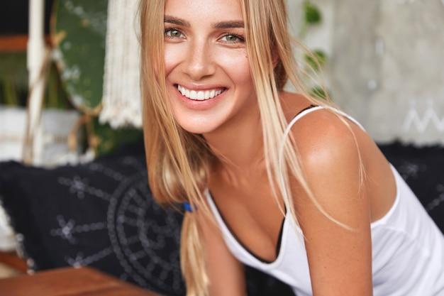 Милая улыбающаяся молодая женщина с привлекательной внешностью, с широкой улыбкой, радостно смеется, слышит позитивные новости от друга, приятно беседует вместе в уютной домашней атмосфере.