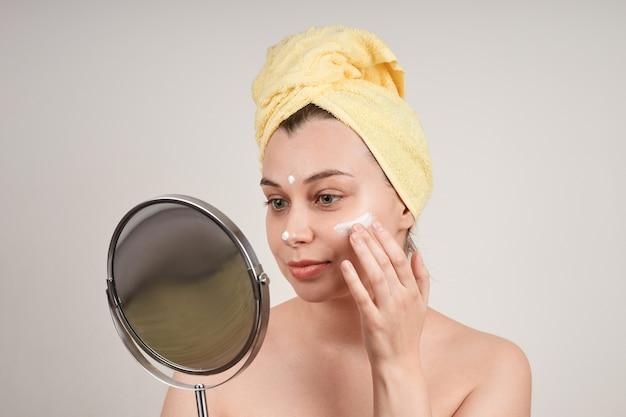 裸の肩、彼女の頭に黄色いタオル、彼女の顔にクリームを適用し、鏡を見て、灰色の壁で隔離のかわいい笑顔の若い女性。