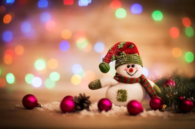 赤と緑の帽子とスカーフとクリスマスボールでかわいい雪だるま