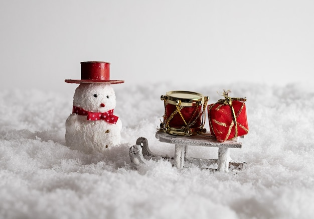 Cute snowman toy, sleigh, and colorful gift boxes in the snow