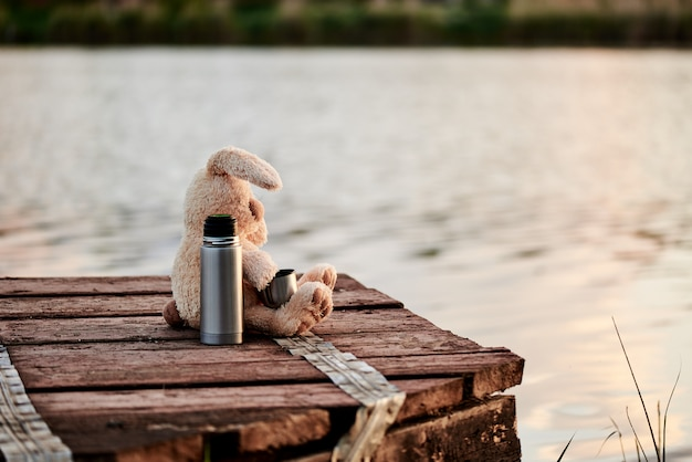 Cute soft rabbit with a thermos on the pier near the lake. copy space.