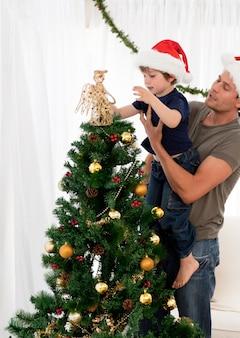 Симпатичный сын, украшающий елку с отцом