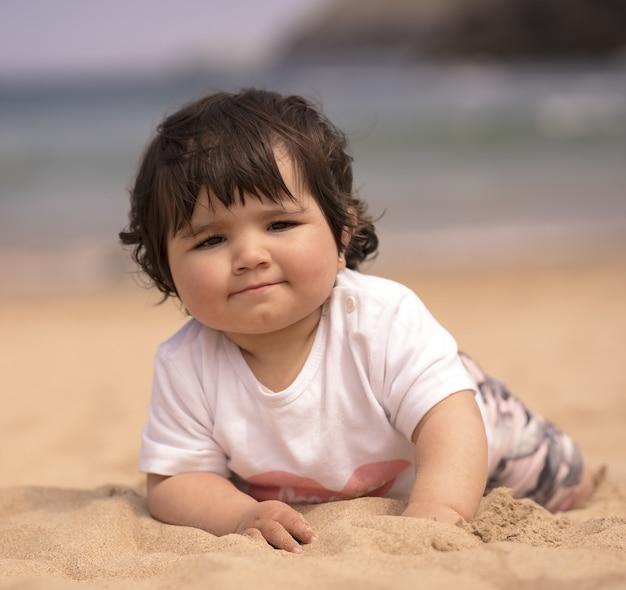 모래 해변에서 노는 귀여운 스페인 아기