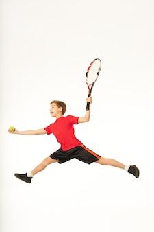 スタジオでジャンプしてテニスをしているかわいいスポーティーな男の子