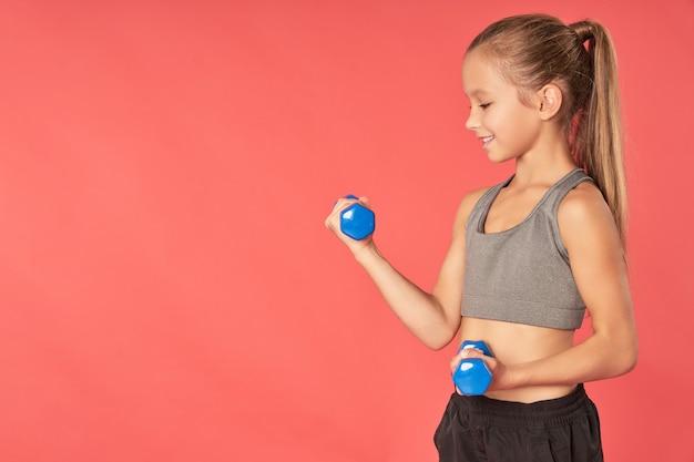 Симпатичная спортивная девушка делает упражнения с гантелями