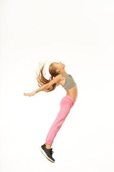 空を飛んでいるかのように見上げてジャンプするピンクのスポーツパンツのかわいいスポーティな女の子。白い背景で隔離