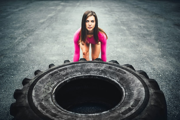 Cute sporty girl lifting huge tire outdoor