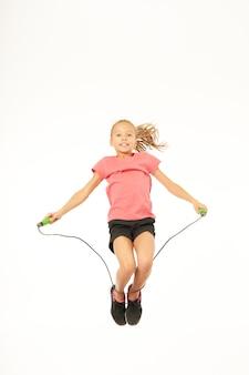 Милая спортивная девушка смотрит в камеру и улыбается, прыгая и используя скакалку. изолированные на белом фоне