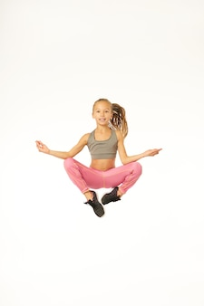 Cute sporty girl looking at camera and smiling while jumping and doing meditation exercise. isolated on white background