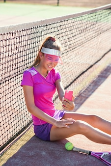 Cute sporty girl sitting on a outdoor tennis court and making video call or conference after tennis training. communication and messaging using smart devices.