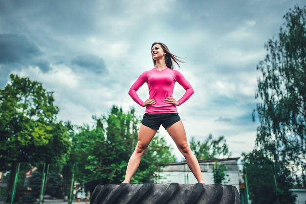 Cute sporty girl standing on huge tire outdoor