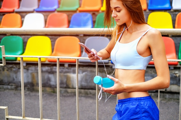 Cute sporty girl with phone and bottle outdoor