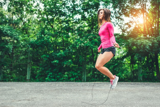 Cute sporty girl with rope training outdoor
