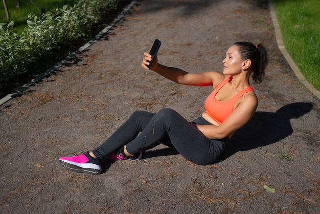 Cute sporty woman having rest and making selfie afer exercising in the city park