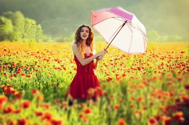 Cute spring girl with umbrella pink color. woman in field of red poppy.
