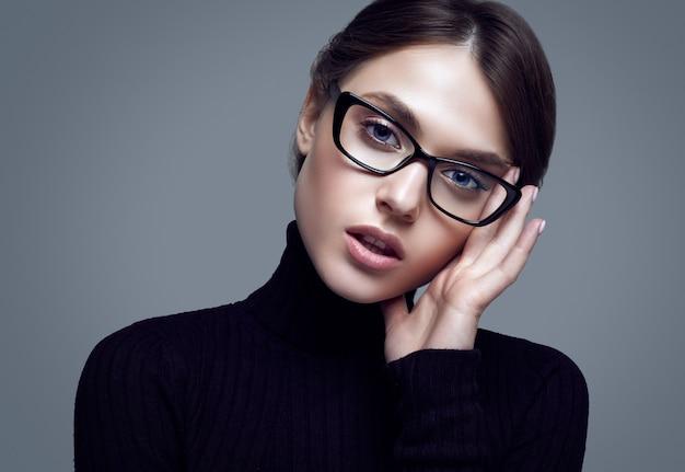 黒のタートルネックのセーターとスタイリッシュな眼鏡を着ているかわいい学生の女の子