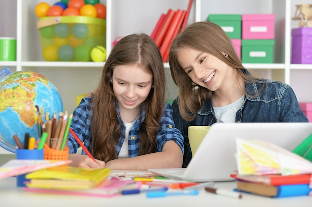 Симпатичные студентки в классе с ноутбуком и чаем