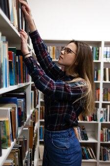 メガネをかけたかわいい学生が図書館の本棚から本を受け取ります。