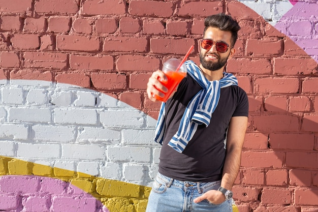 口ひげとあごひげを生やし、ストローでジュースを飲む眼鏡をかけているかわいいスタイリッシュなアラブの若い男性のヒップスター。夏休みのコンセプト。