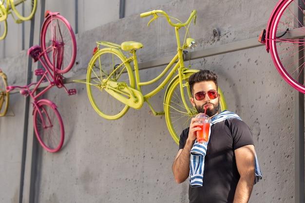 Симпатичный стильный арабский молодой хипстер с усами и бородой в очках, пьющий сок