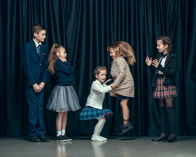 Bambini alla moda carino su uno spazio buio. le belle ragazze adolescenti e ragazzo che stanno insieme Foto Gratuite
