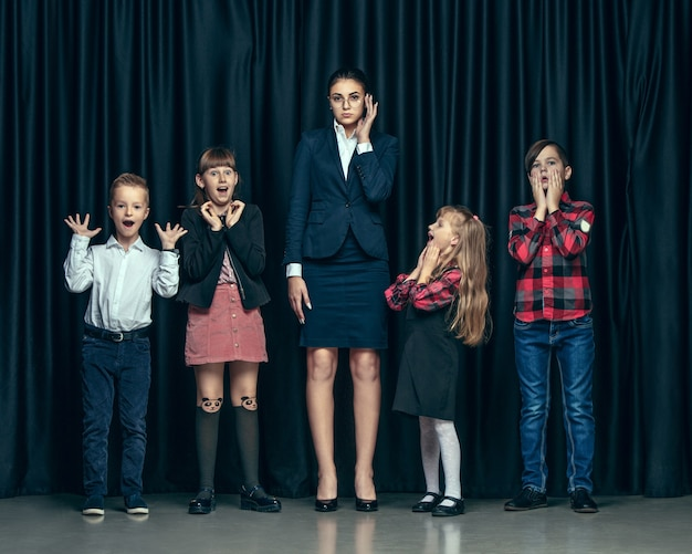 Cute stylish children on dark studio background. the beautiful teen girls and boy standing together