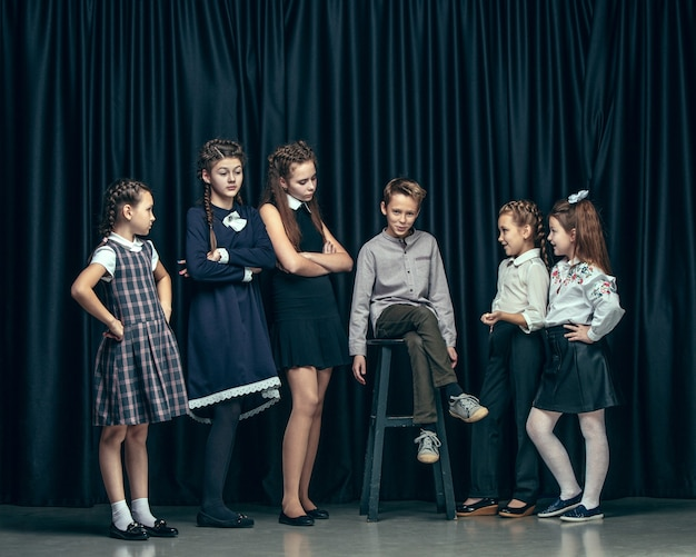 Cute stylish children on dark studio background. the beautiful teen girls and boy standing together