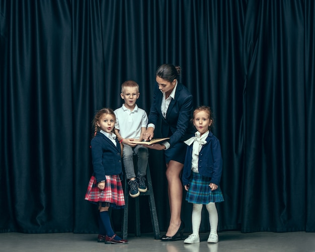 Cute stylish children on dark studio. the beautiful teen girls and boy standing together