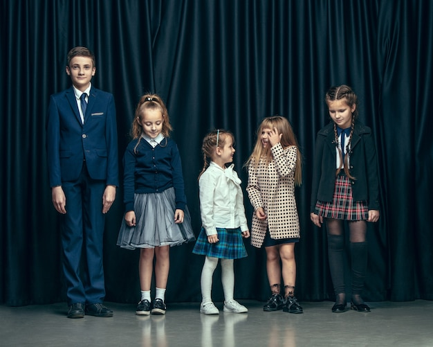 Cute stylish children on dark studio. the beautiful teen girls and boy standing together