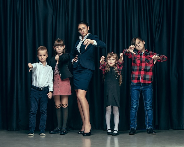 Cute stylish children on dark studio wall. the beautiful teen girls and a boy standing together