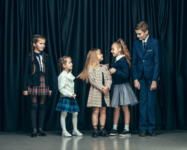 어둠에 귀여운 세련된 아이들. 아름 다운 십 대 소녀와 함께 서있는 소년